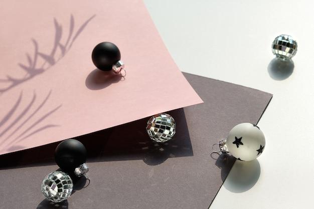 Close-up em brinquedos de natal em preto e branco e bolas de espelho em papel em camadas rosa e cinza.