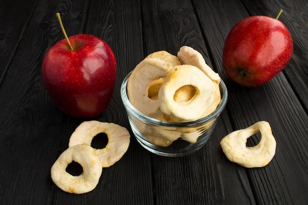 Close-up em chips de maçã em uma tigela de vidro e maçãs vermelhas