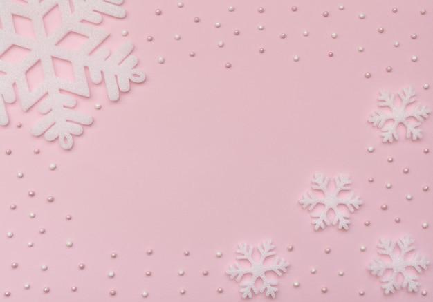 Close-up em flocos de neve brancos em papel rosa