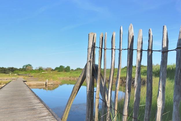 Close-up em frence de madeira natural e passarela cruzando lagoas de água do mar sob o céu azul