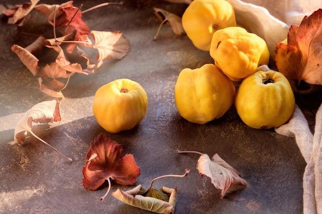 Close-up em frutos maduros de marmelo japonês doce na mesa escura com torre de linho.