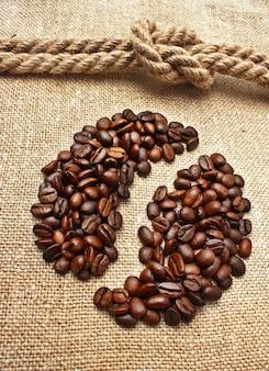 Close-up em grãos de café e nó de corda no saco