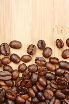 Close-up em grãos de café em um fundo de madeira Foto Premium