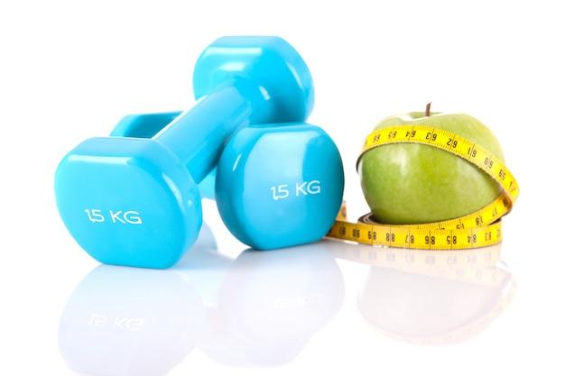 Close-up em halteres azuis com maçã e fita métrica isolada