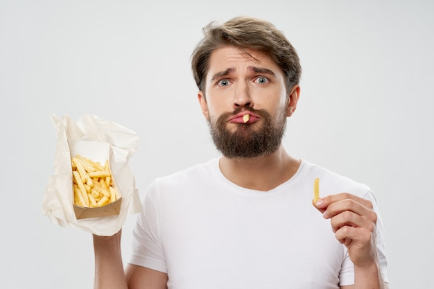Close-up em homem comendo batata frita isolada