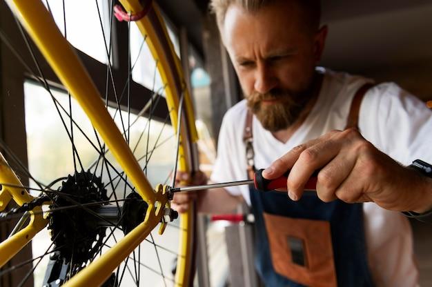 Close-up em jovem trabalhando em uma bicicleta
