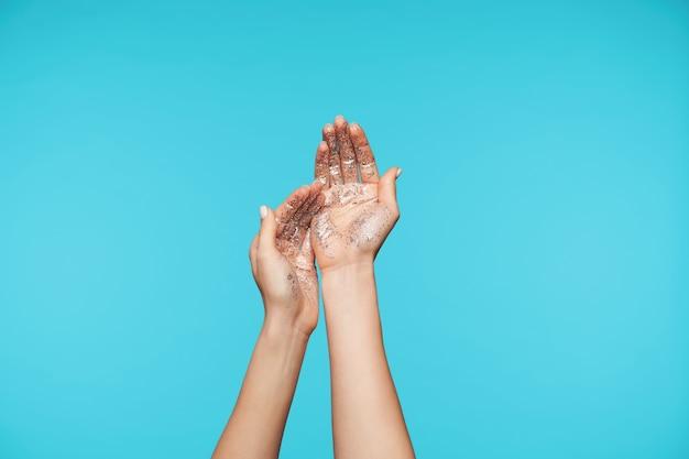 Close-up em mãos levantadas com brilhos esfregando-as enquanto lava os braços