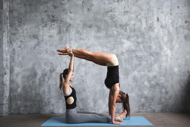 Close-up em mulheres de ioga de fitness no tapete no ginásio
