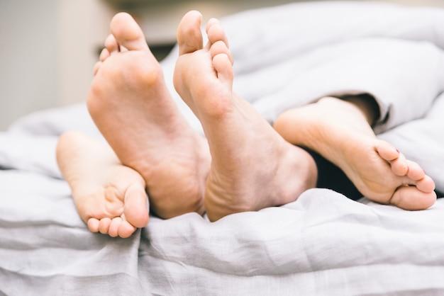 Close-up em pés de casal saindo do cobertor