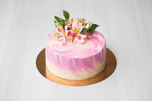 Close-up em um bolo com decoração rosa e flores
