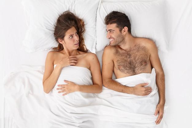 Close-up em um casal deitado na cama sob um cobertor branco