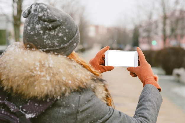 Close-up em um celular em branco, seguro na mão