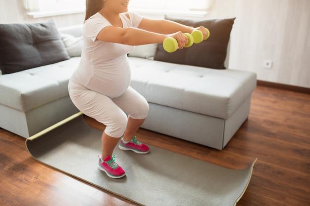 Close-up em um haltere. mulher grávida com halteres. vida esportiva ativa, bem-estar.