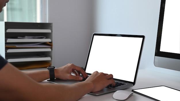 Close-up em um jovem usando um laptop para pesquisar informações na internet