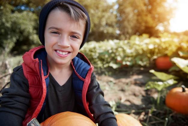 Close-up em um menino jovem e feliz segurando uma abóbora