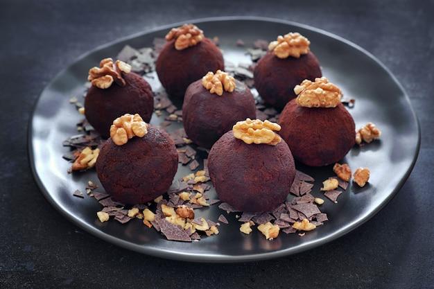 Close-up em um prato escuro de bolas de rum decoradas com nozes