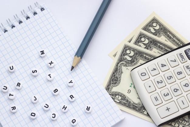 Close-up, em uma calculadora de fundo branco, dinheiro e um bloco de notas com letras
