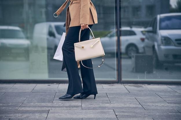 Close-up em uma elegante mulher caucasiana magra com sacolas de compras andando na rua