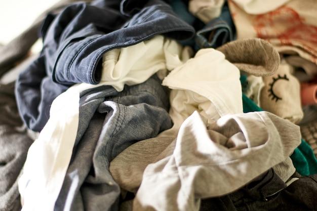 Close-up em uma grande pilha de roupas e acessórios jogados no chão