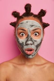 Close-up em uma jovem mulher bonita com máscara facial Foto gratuita