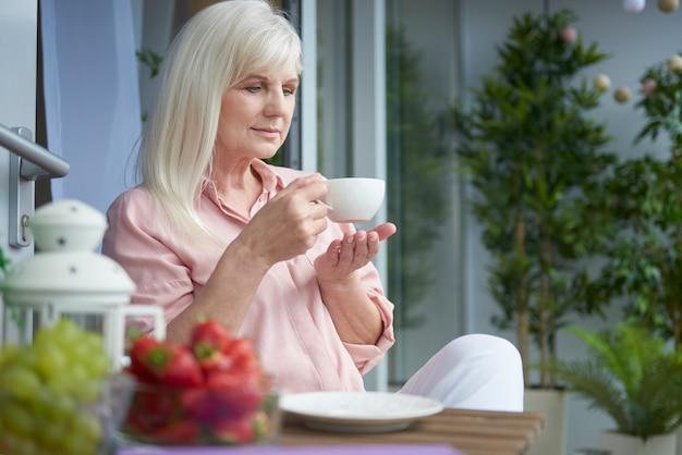 Close-up em uma mulher madura tomando um bom café na varanda Foto gratuita