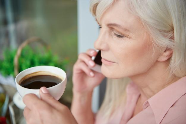 Close-up em uma mulher madura tomando um bom café na varanda