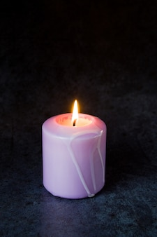 Close-up em uma vela roxa acesa isolada