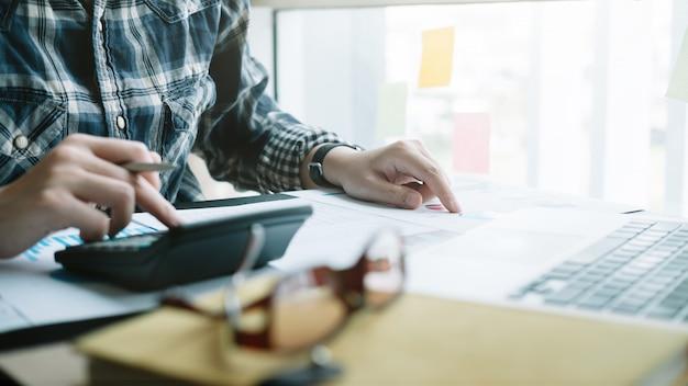 Close-up, empresária, analisando o relatório de dados financeiros