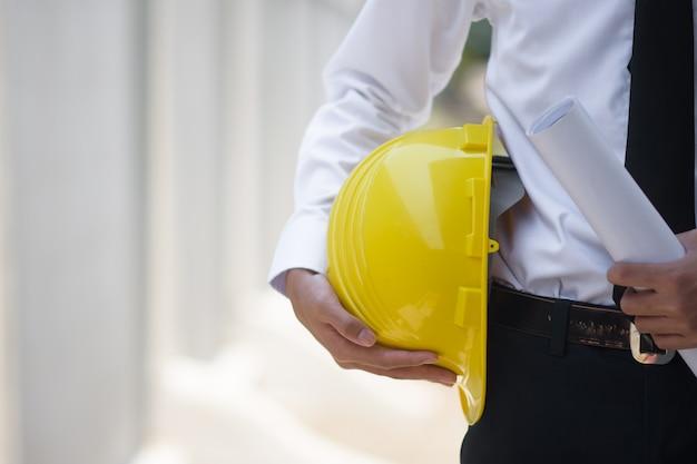 Close-up empresário segurando capacete amarelo construtor construção imobiliário