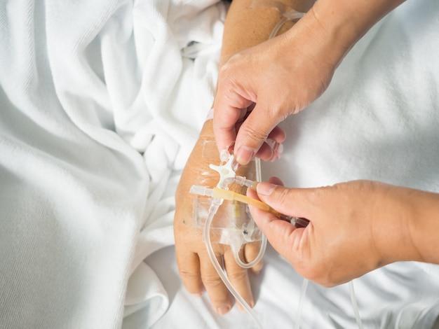 Close-up enfermeira mão ajustar três vias de iv conjunto para gotejamento intravenoso de gota salina fluida em branco