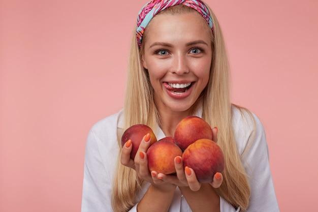 Close-up engraçado de uma bela loira em pé, animada com os pêssegos nas mãos, sorrindo amplamente e mostrando a língua