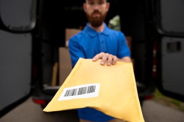 Close-up entregador segurando pacote
