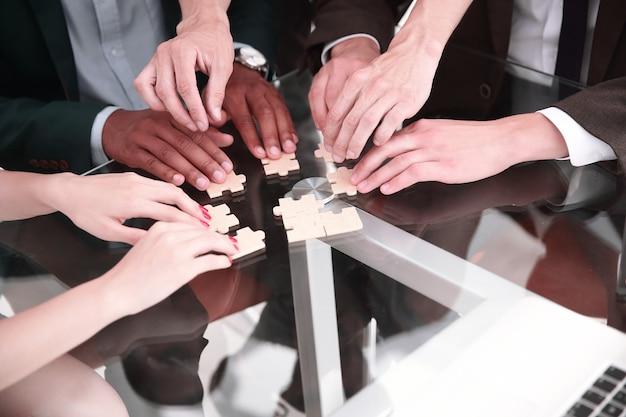 Close up. equipe de negócios multinacionais montando quebra-cabeça. o conceito de estratégia nos negócios