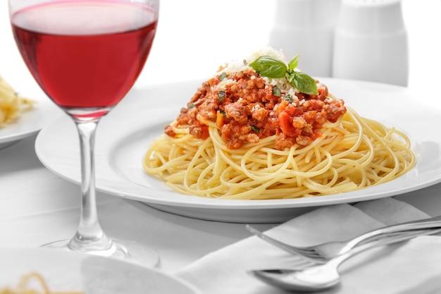 Close-up espaguete italiano à bolonhesa servido com uma taça de vinho tinto