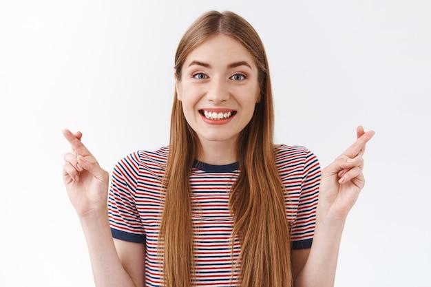 Close-up esperançosa, positiva e fofa mulher caucasiana em uma camiseta listrada, acredita que os sonhos se tornam realidade, aguardando admissão na universidade, cruze os dedos, boa sorte, sorrindo positivo, fundo branco