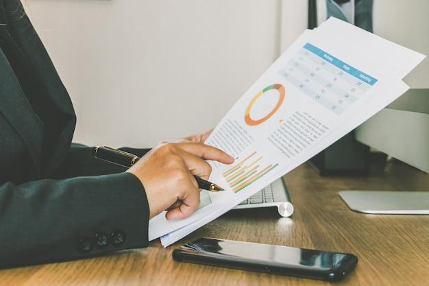 Close-up, executiva, leitura, e, verificar, volume de negócios, documentos, ligado, dela, escrivaninha