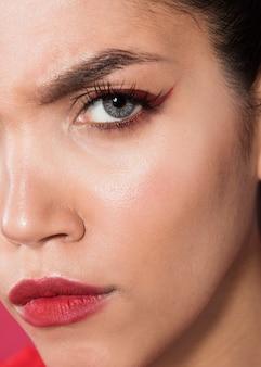 Close-up extremo tiro modelo sério usando maquiagem