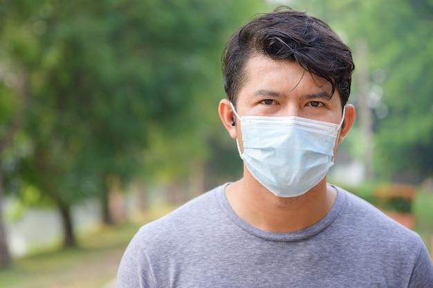 Close-up face focus homem jovem bonito asiático pessoas que suam com os exercícios matinais e usam uma máscara com sars-cov-2.