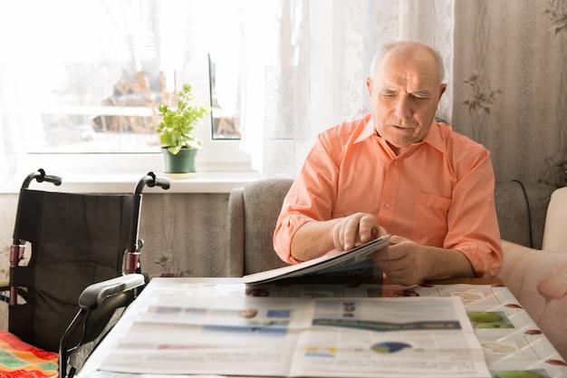 Close-up feliz atualizado sênior lendo jornal na mesa na sala de estar com sua cadeira de rodas ao lado.