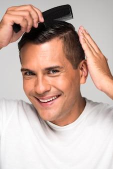 Close-up feliz do homem usando um pente de cabelo
