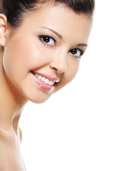 Close-up feliz e sorridente com o rosto de uma mulher asiática atraente isolada no branco