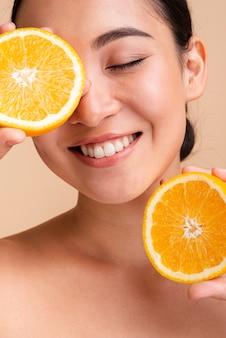 Close-up feliz mulher asiática com laranja