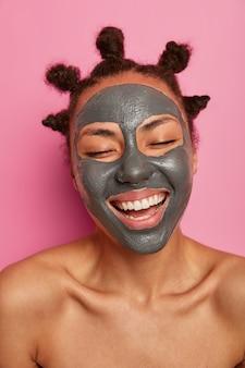 Close-up, feliz mulher étnica gosta de aplicar máscara facial isolada