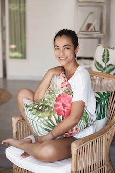 Close-up feliz mulher jovem e saudável com cabelo escuro encaracolado, sentada em um sofá confortável em um terraço