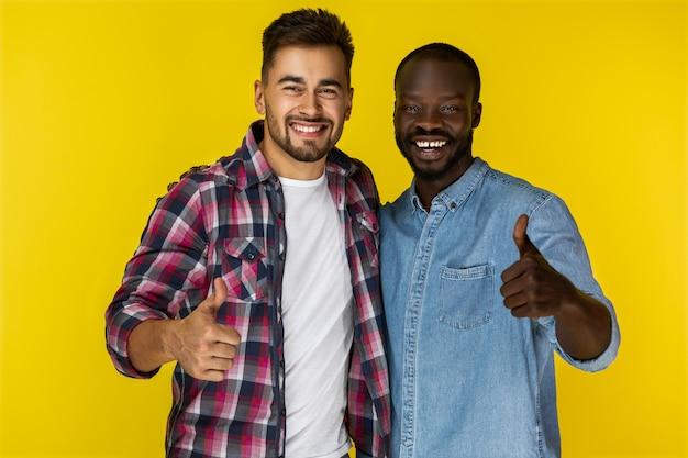 Close-up felizes europeus e negros, mostrando os polegares