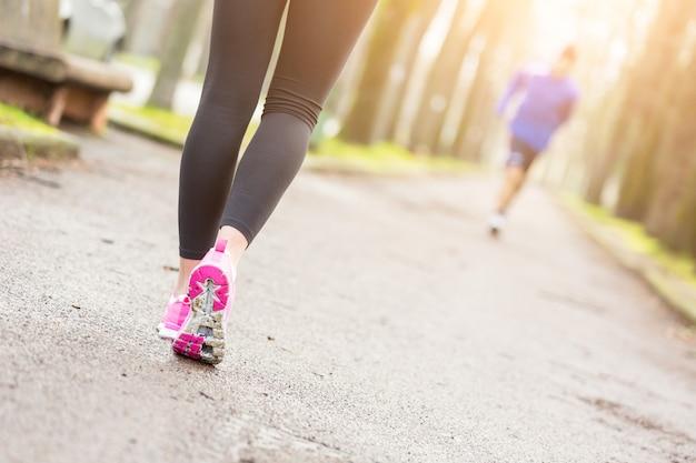 Close up fêmea dos calçados do corredor antes de correr no parque.