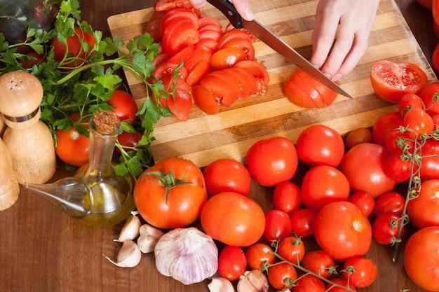 Close up, femininas, mãos, fatiar, tomates