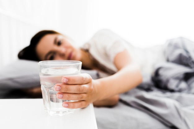 Close-up feminino mão alcançando o copo de água