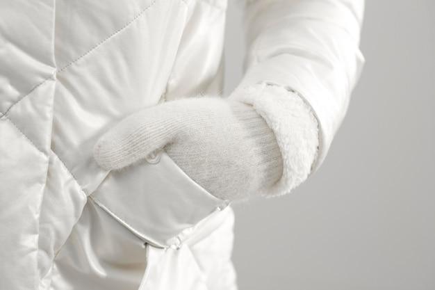 Close-up feminino usando luvas e segurando a mão no bolso