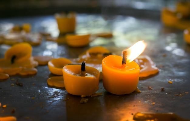 Close-up flamejante de cera no templo para iluminação e oração